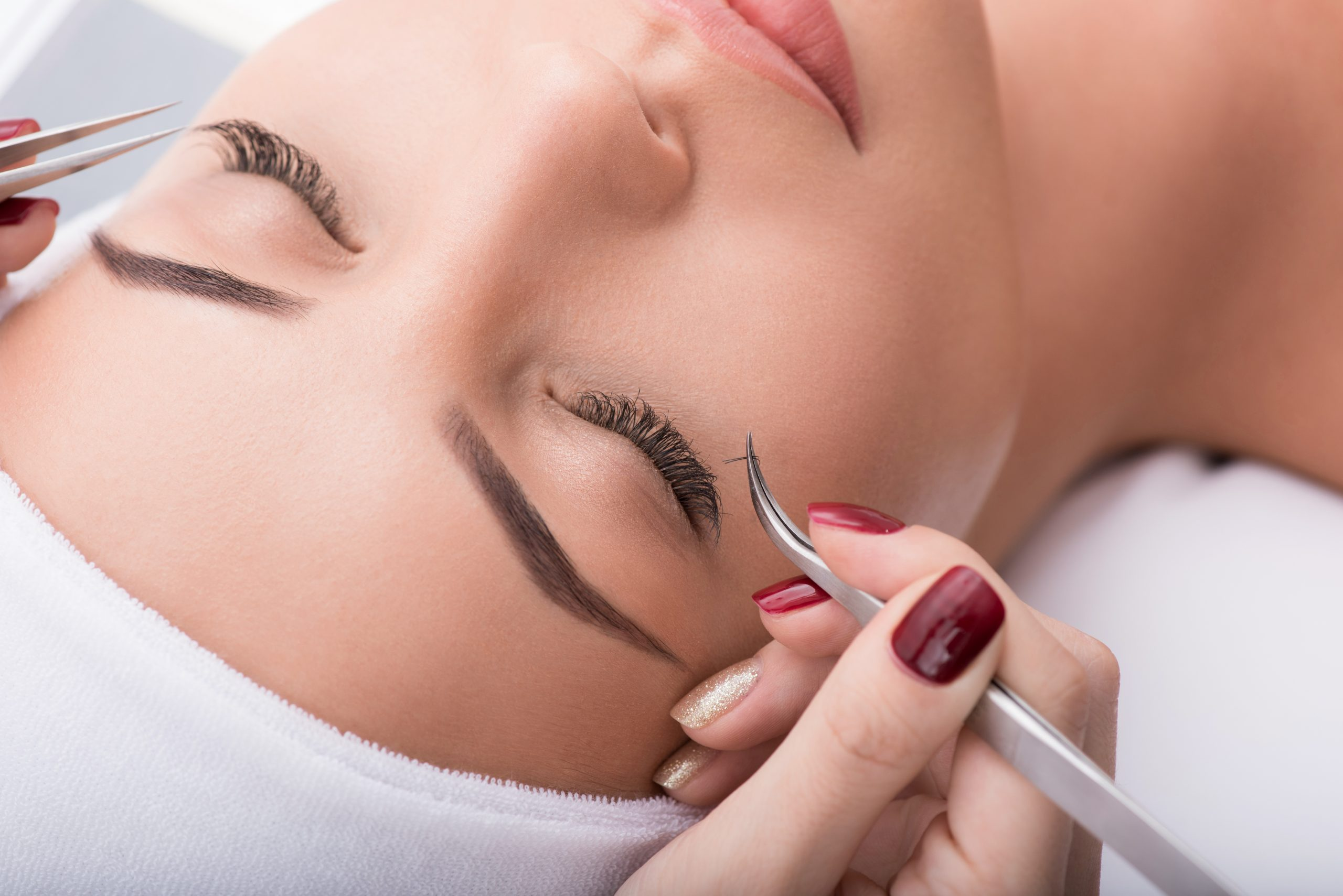 Close up of female face. Beautician building up long artificial eyelashes for young woman