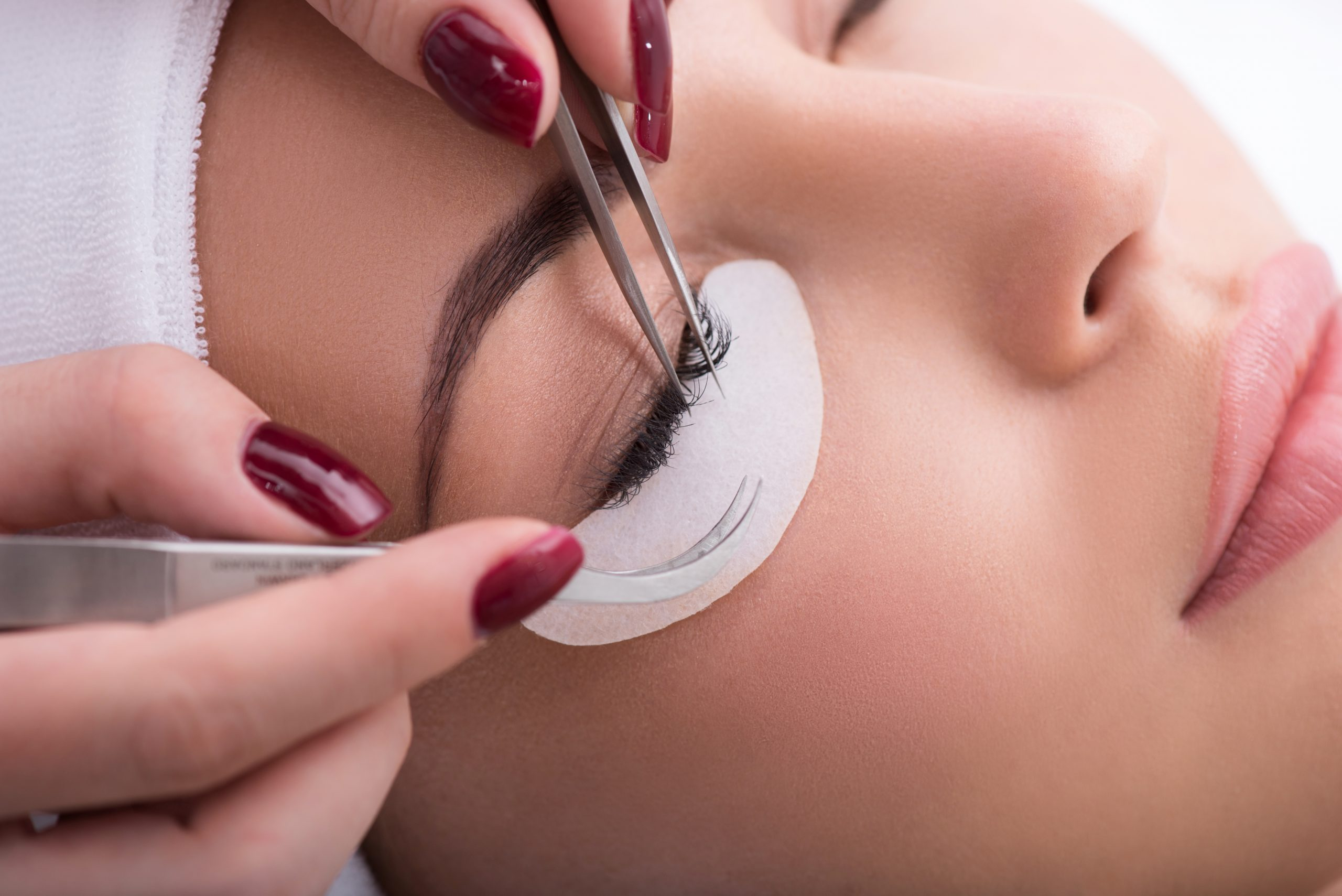 Skillful beautician is undergoing eyelash extension procedure. Close up of female face