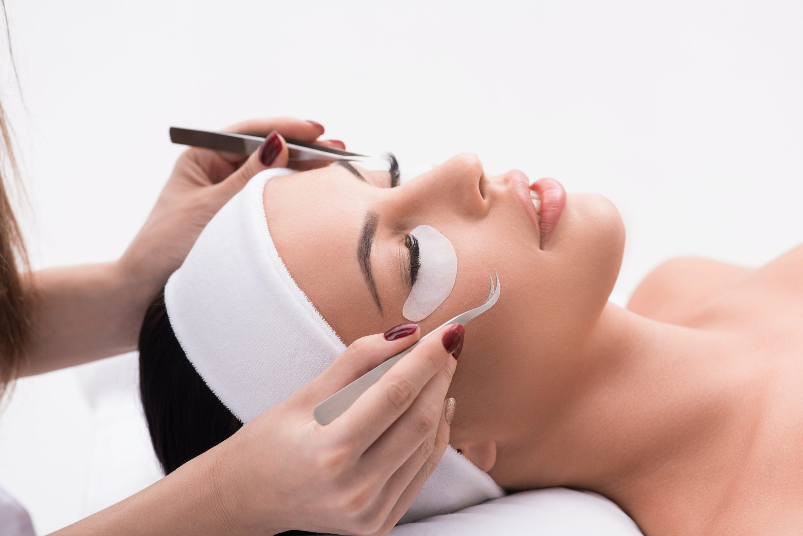 Close up of beautician arms making artificial lashes at beauty salon. Young woman is lying with relaxation and smiling